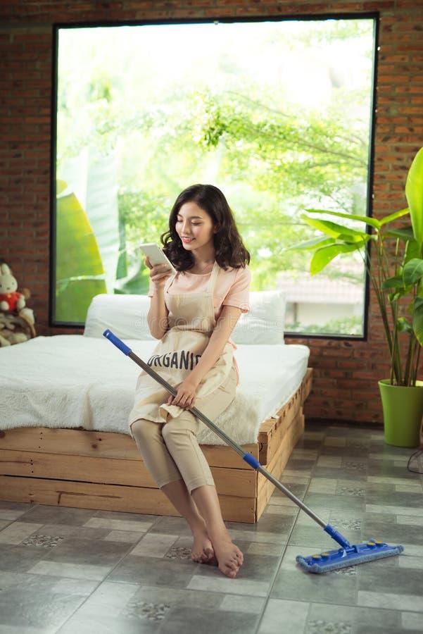 Housekeeping pojęcie Kobieta texting podczas gdy robić sprzątaniu zdjęcia royalty free