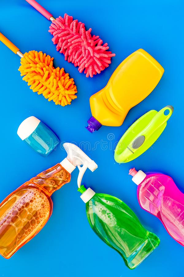 Housekeeping set. Detergents, soap, cleaners and brush for housecleaning on blue background top view mock-up stock photo