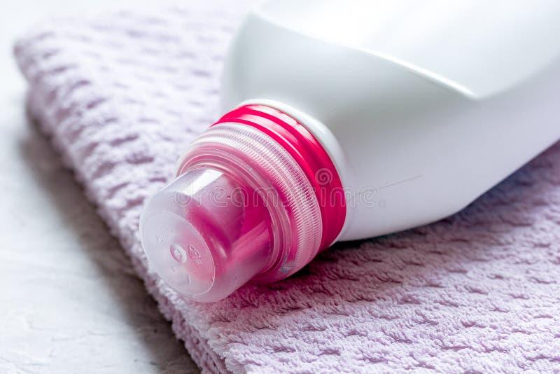 Housekeeping ustawiający z ręcznikami i klingeryt butelkami w pralni na kamiennym tle zdjęcia royalty free