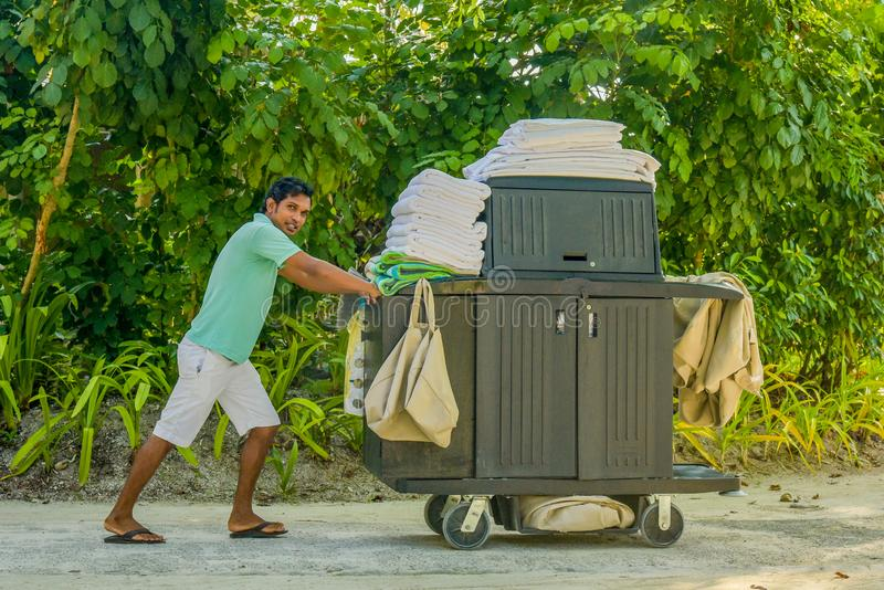 Housekeeping worker pushing the cart with cleaning tools royalty free stock photos