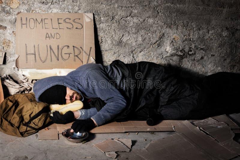 Houseless Mann, der auf der Straße mit Almosenkasten schläft stockfoto