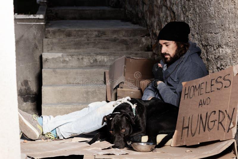 Houseless Mann, der mit seinem Hund auf Hintergasse sitzt stockbild