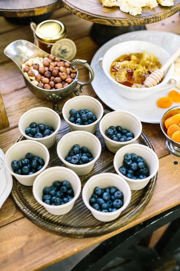 Housemade, meal, dessert concept. table setting with numbers of such treats as nuts, berries, dried apricots, nearby stock photo