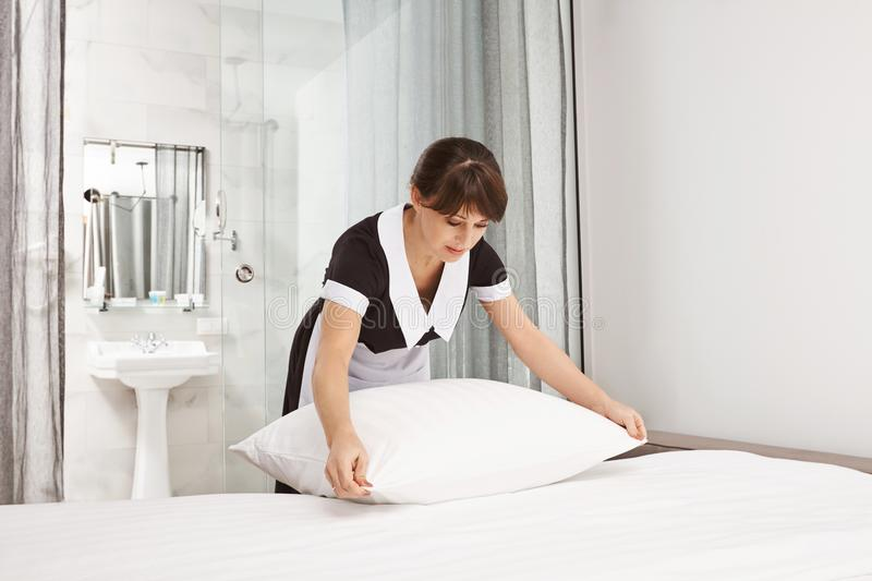 Housemaid beating pillows in hotel room. Portrait of nice neat lady who works as maid making bed while owners of house stock image
