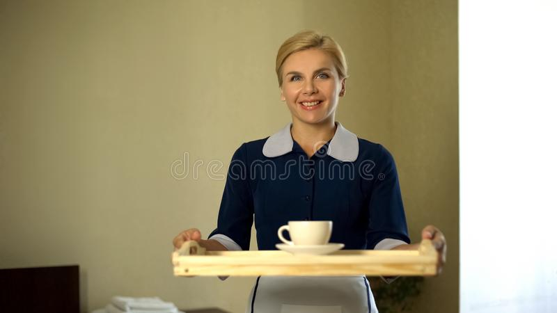 Housemaid bringing tray with coffee, good service, 5star hotel room booking stock photos