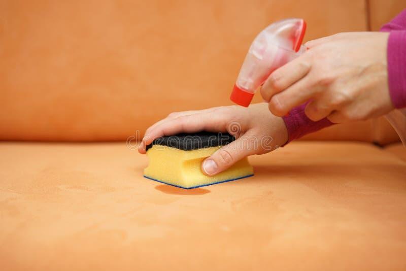 Housemaid czyści plamę na kanapie z kiści gąbką i butelką obraz stock