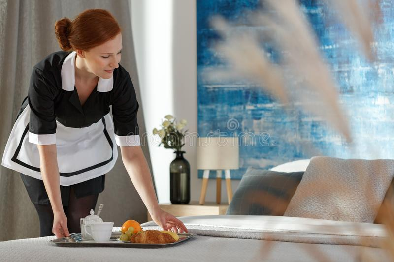 Housemaid putting tray with food. Housemaid putting a tray with food on a hotel room bed in the morning royalty free stock photo