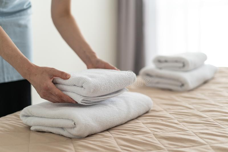 Housemaid woman holding white towels in hands stock photos