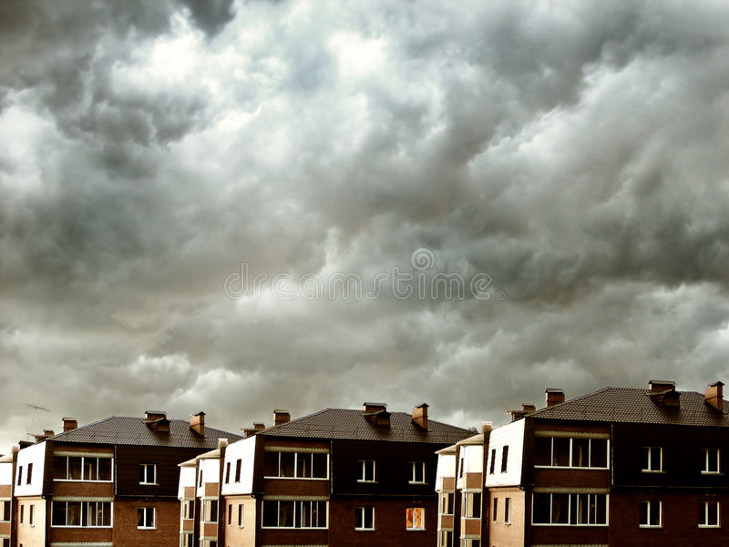 Houses against dark clouds. Block of flats stand out against a dark storm clouds background stock photography