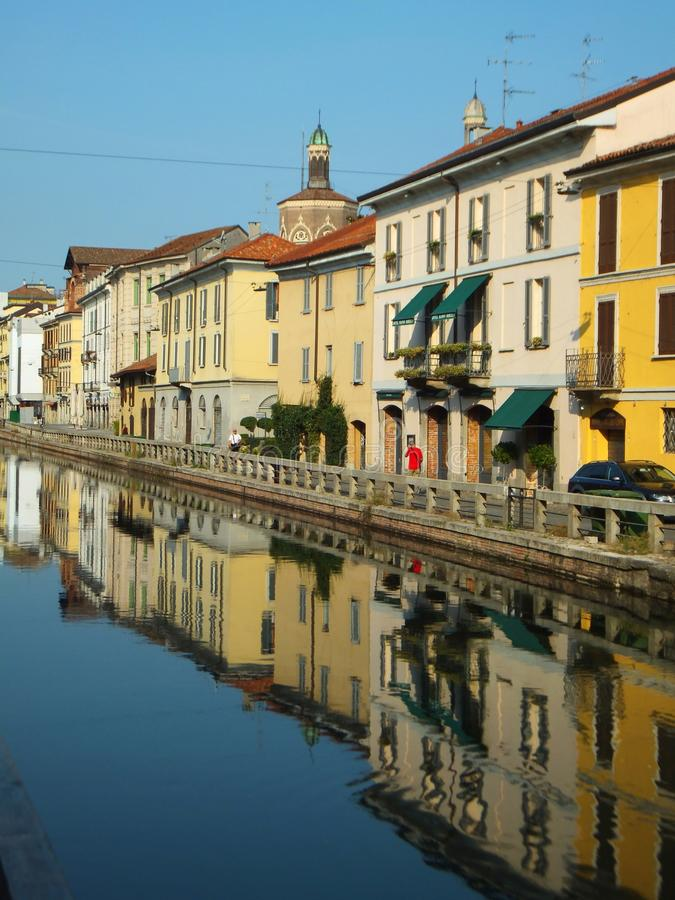 Houses along the Naviglio Grande in Milan on a bright summer morning, reflected in the calm water of the canal royalty free stock images