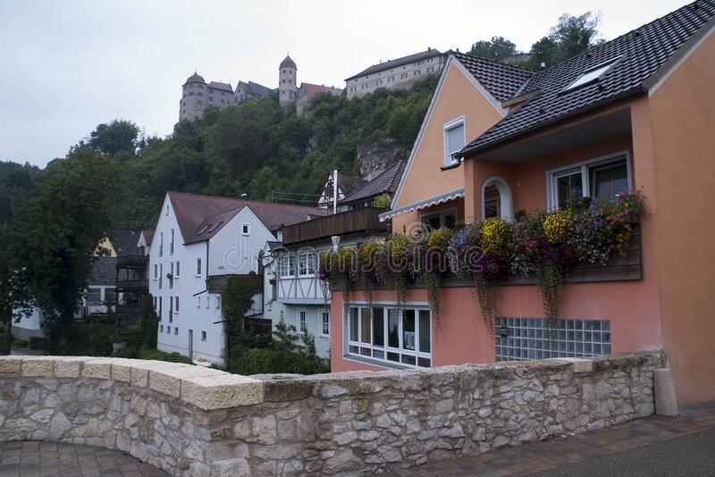 Houses along river with castle in background royalty free stock photo