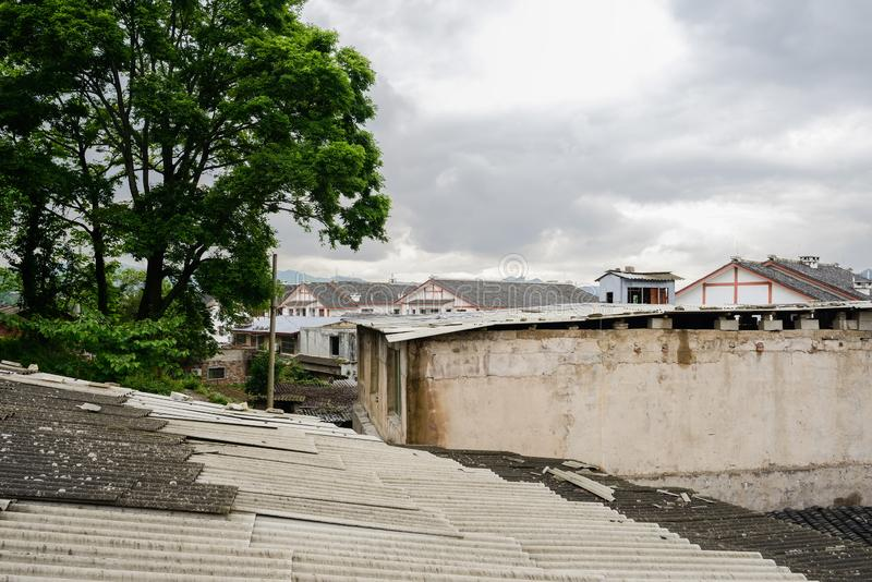 Houses with asbestos shingles in Qingyan ancient town on cloudy. Dwelling buildings with asbestos shingles before traditional buildings on cloudy spring day royalty free stock image