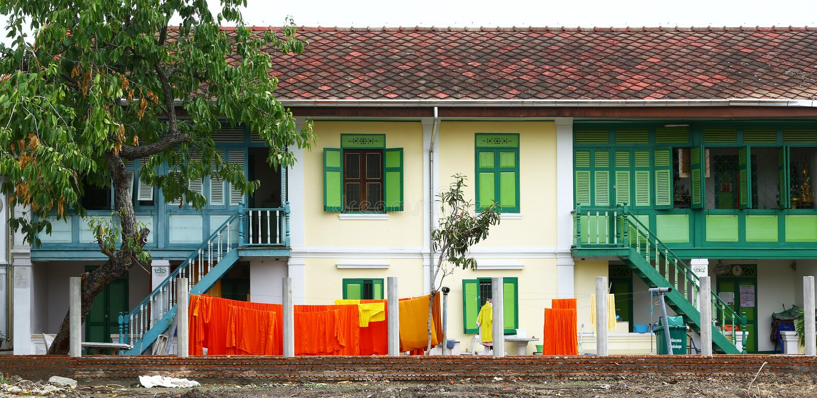 Houses of buddhist monks in Bangkok, Thailand. Their laundry, made of bright orange dresses, is hanging out to dry stock photos