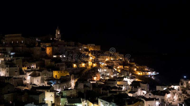 Houses built into the rock with cathedral at the top of the hill, in the cave city of Matera, Sassi di Matera, Basilicata Italy. Matera has been designated royalty free stock photo