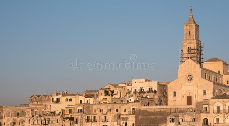 Houses built into the rock with cathedral at the top of the hill, in the cave city of Matera, Sassi di Matera, Basilicata Italy. Matera has been designated royalty free stock photography