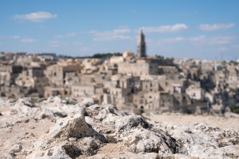 Houses built into the rock in the cave city of Matera, Basilicata Italy. Rock of the ravine in foreground. Houses built into the rock in the cave city of Matera stock photography