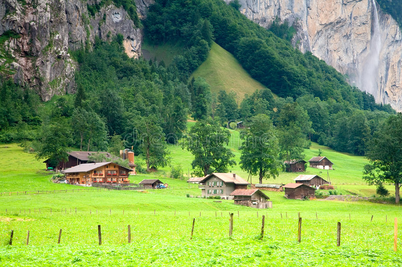 Houses close to a Steep Rocky Mountain. Houses and barns are close to a steep rocky mountain near Lauterbrunnen, Bern Canton, Switzerland royalty free stock image