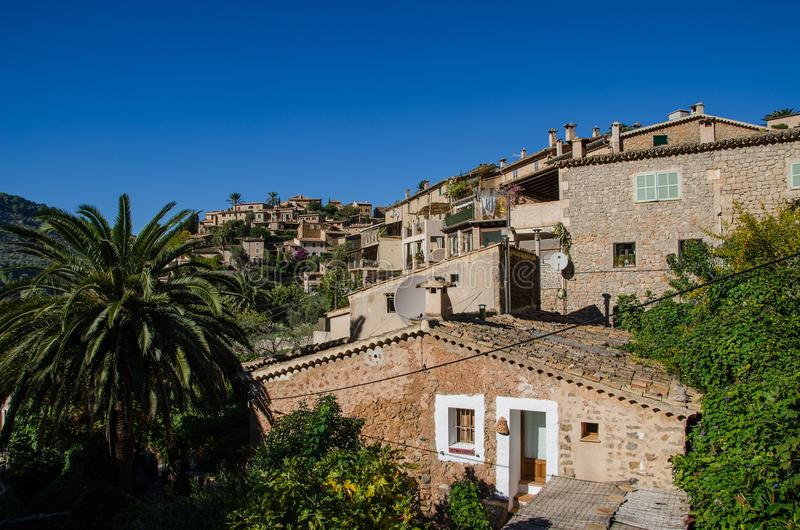 Houses of Deia. View of the central hill in Deia, Mallorca, Spain. Village Deia in tramuntana mountains Mallorca. The hill is surrounded by greenery. Deia is a stock photo