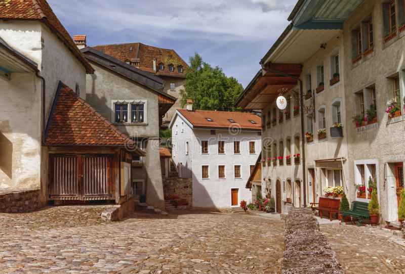 Houses in Gruyeres village, Fribourg, Switzerland. Houses and street in Gruyeres village by day, Fribourg, Switzerland royalty free stock image
