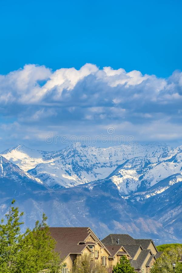 Houses and lush green trees with snow capped mountain in the background. Bright blue sky with thick gray clouds can be seen overhead on this sunny day stock photography