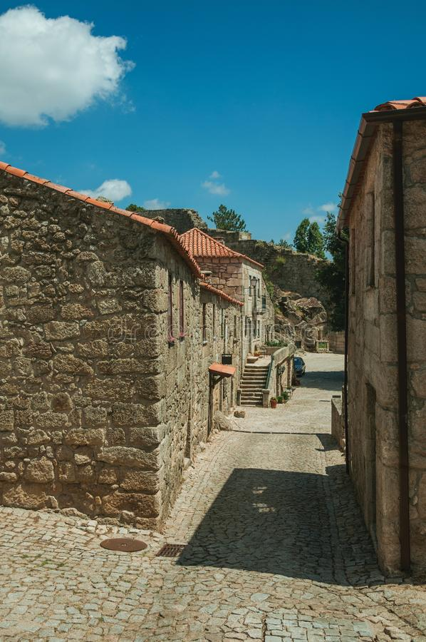 Houses made of stone with staircase in an alley. Gothic houses made of stone with staircase and deserted alley on slope, in a sunny day at Sortelha. One of the royalty free stock image