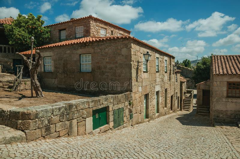 Houses made of stone with staircase in an alley. Gothic houses made of stone with staircase and trees in deserted alley on slope, in a sunny day at Sortelha. One royalty free stock photos