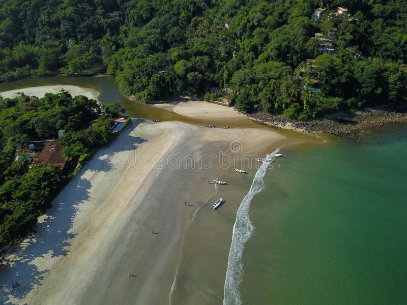 Houses on the mountain near the beach with clear and clean water and the river on the beach of the bar sahy north coast of sao pau royalty free stock images
