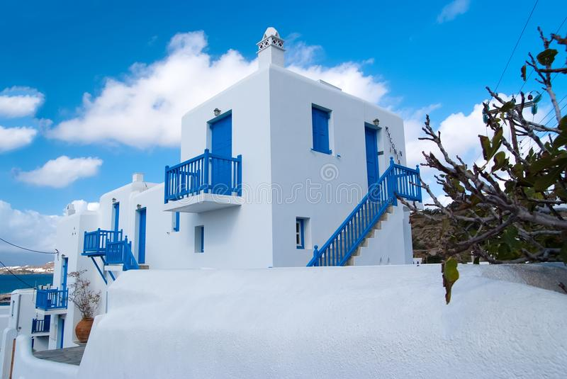 Houses in Mykonos, Greece. Whitewashed buildings with blue painted windows and doors on sunny sky. Typical architecture stock photo