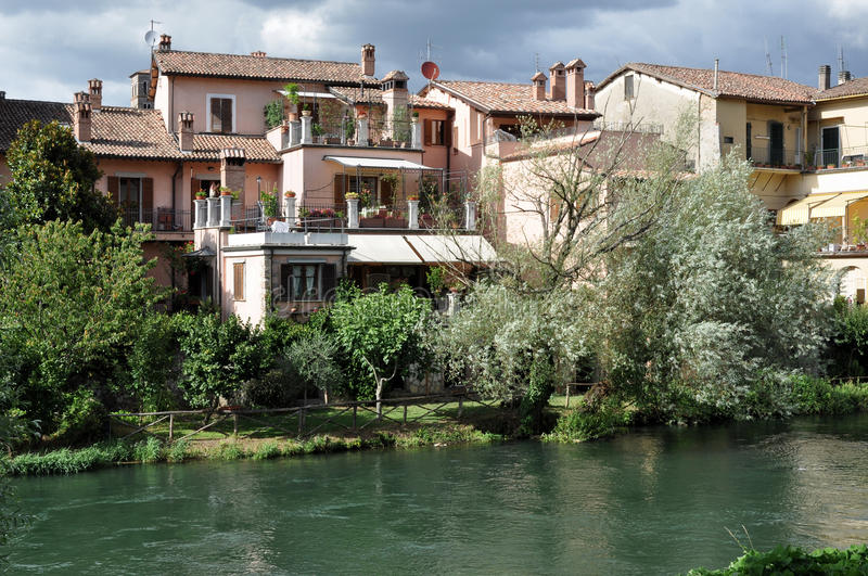 Houses near velino river, rieti. View of old houses in city center near the river, on a summer day with thunderclouds royalty free stock photography