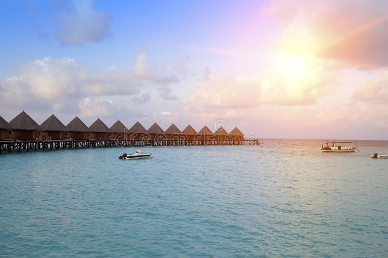 Houses over the transparent quiet sea water on a sunset. Maldives royalty free stock images