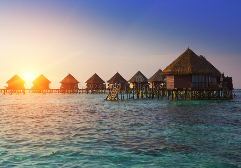 Houses over the transparent quiet sea water on a sunset. Maldives royalty free stock photography