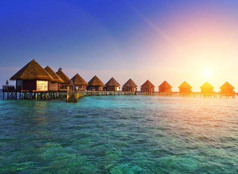 Houses over the transparent quiet sea water on a sunset. Maldives royalty free stock photo
