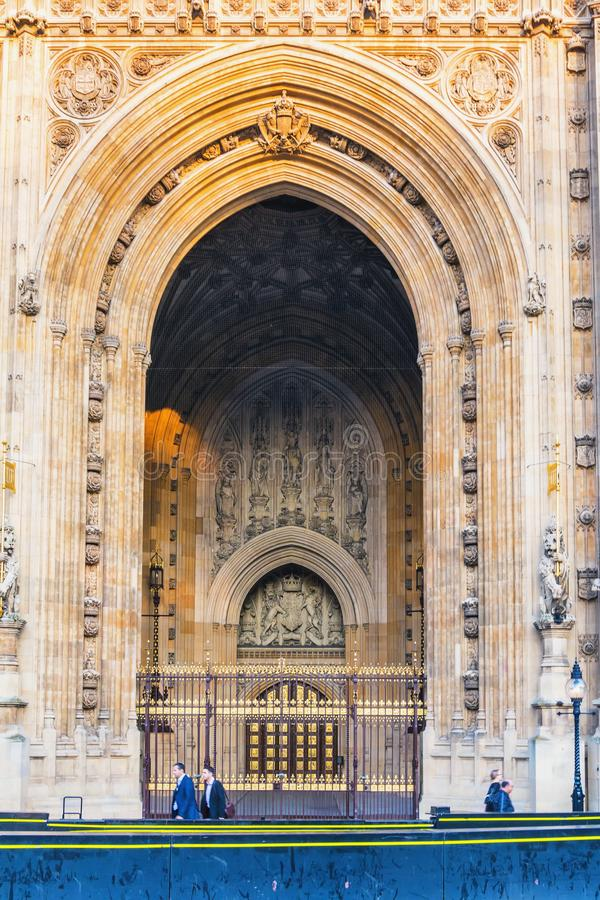 Houses of Parliament Sep 2014 in London. People walkinn in front of old church door and marble antique wall stock photography