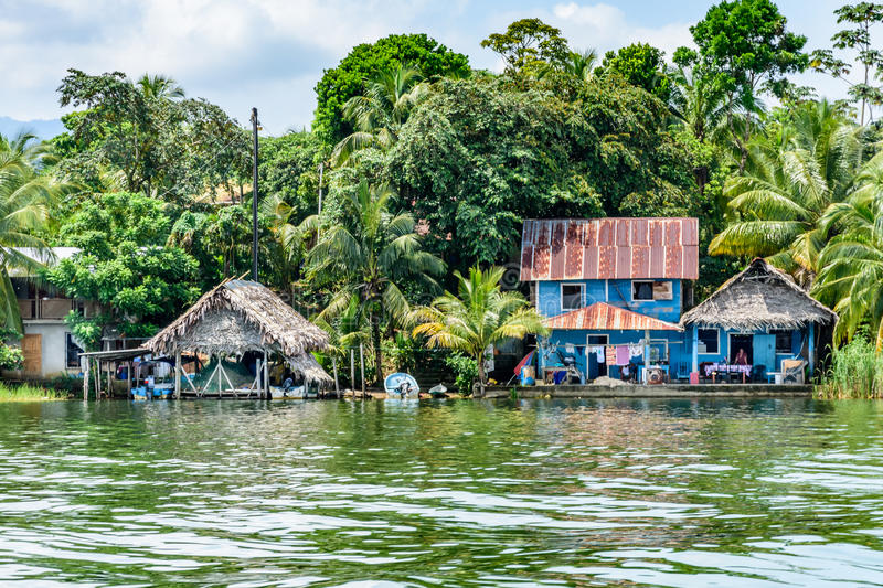 Houses on riverbank of Rio Dulce, Guatemala,. Rio Dulce, Guatemala - September 1, 2016: Wooden houses with tin & palm leaf roofs on riverbank of the Rio Dulce in royalty free stock photography