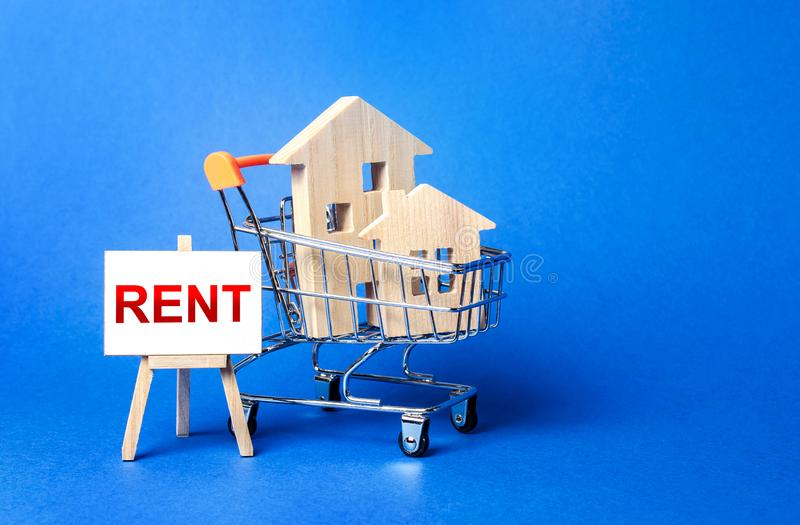 Houses in a shopping cart and an easel with a word Rent. Rental housing and apartments, choice between buying and renting. Real estate prices and the stock images