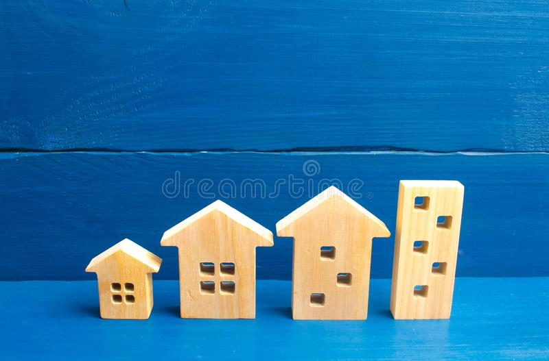 Houses stand in a row from simple to large. Concept of urbanization and population density. The growth of cities, the construction. Of high-rise buildings royalty free stock photo
