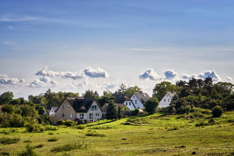 Houses under the clouds on the island Hiddensee. Panorama of Hiddensee. Cloudscape, landscape, baltic, sea, meadow, nature, baltic-sea-island, mecklenburg stock photos