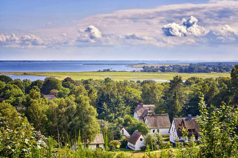 Houses under the clouds with a view of the Baltic Sea. Panorama of Hiddensee. Cloudscape, island, valley, landscape, meadow, nature, baltic-sea-island stock images