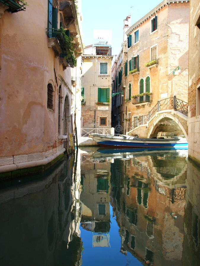 Houses in Venice, Italia. Colorful narrow lateral canal, church Santa Maria dei Miracoli and pedestrian bridge in the sestiere of Cannaregio at morning, in royalty free stock image