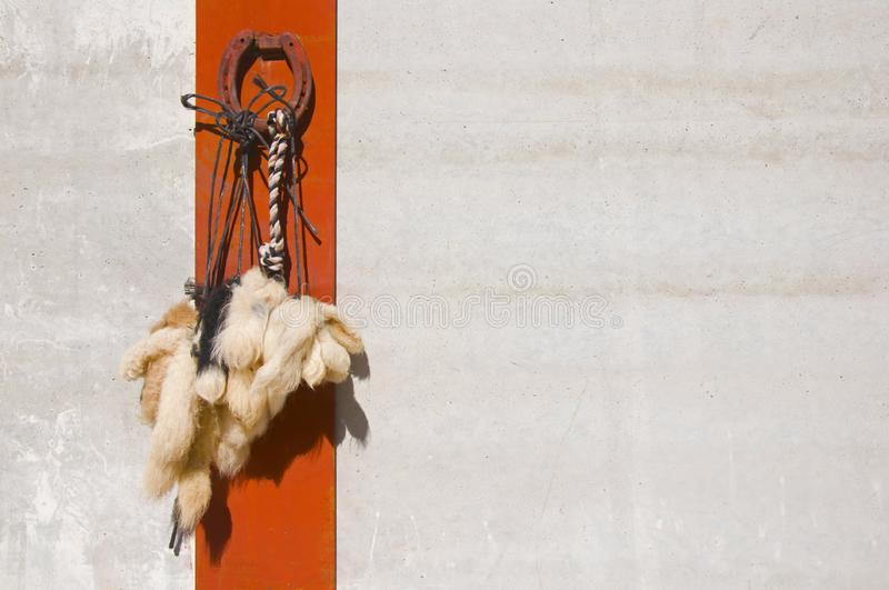 Houseshoe and woolen tails as a talisman for a good luck on the white wall with red line background stock photo