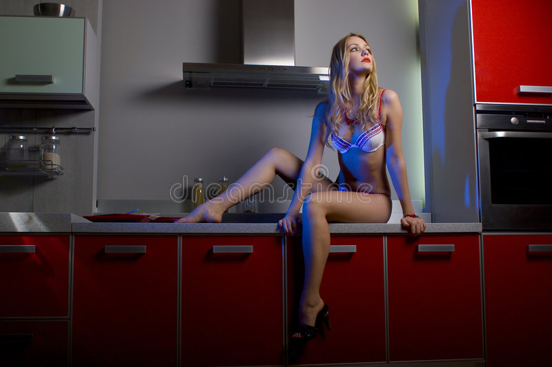 *The housewife*. The blonde in underwear on red kitchen stock photos