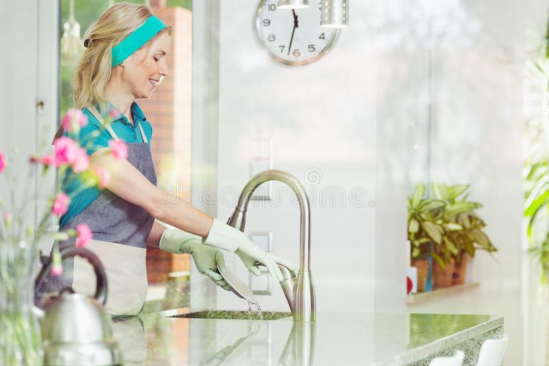 Housewife in apron washing dishes stock photo