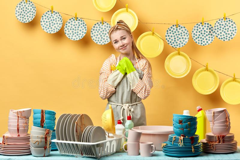 Beautiful young cheerful housewife asking to help her to wash the dishes stock photo