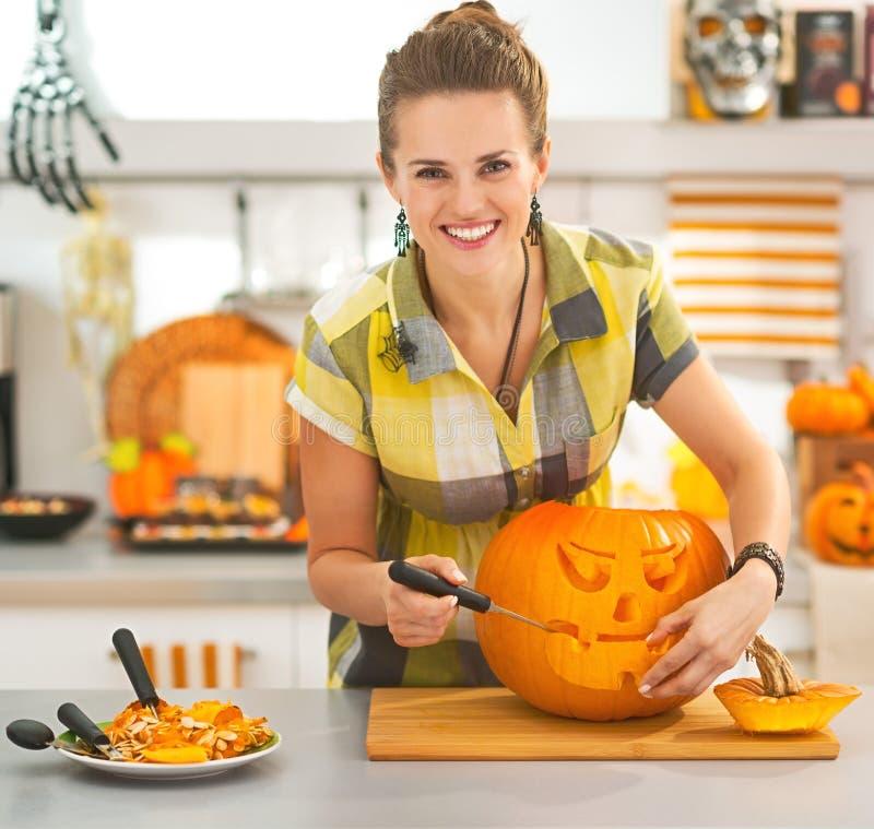 Housewife carving a big orange pumpkin Jack-O-Lantern in kitchen royalty free stock image