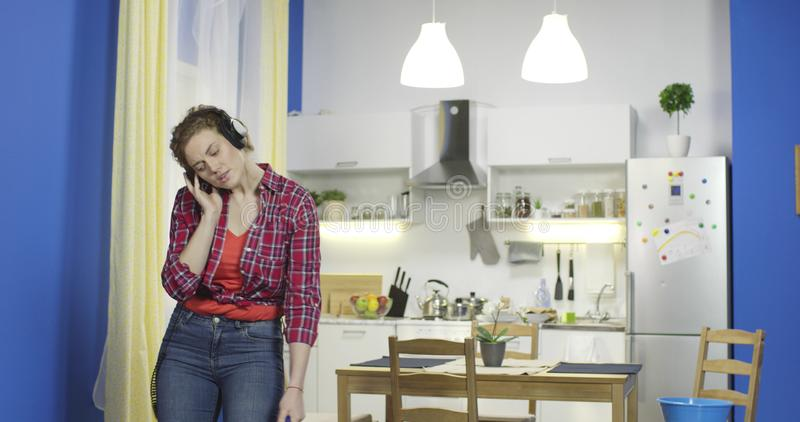 Housewife cleans at the kitchen and sings along in a loud voice. stock photography
