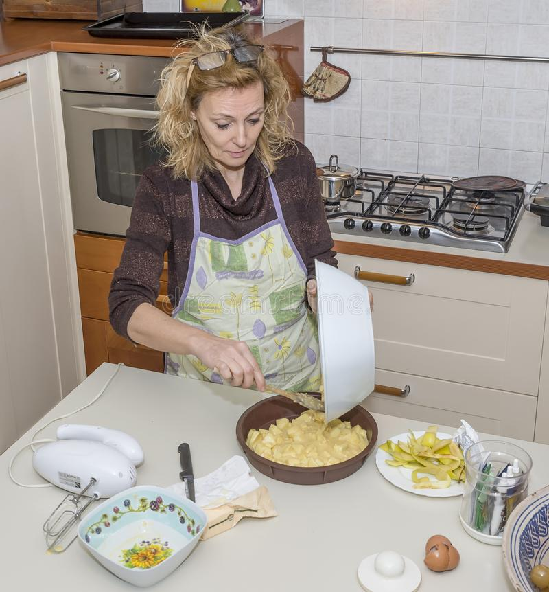 Housewife concentrated in pouring a dough of apple dessert into the mold stock images