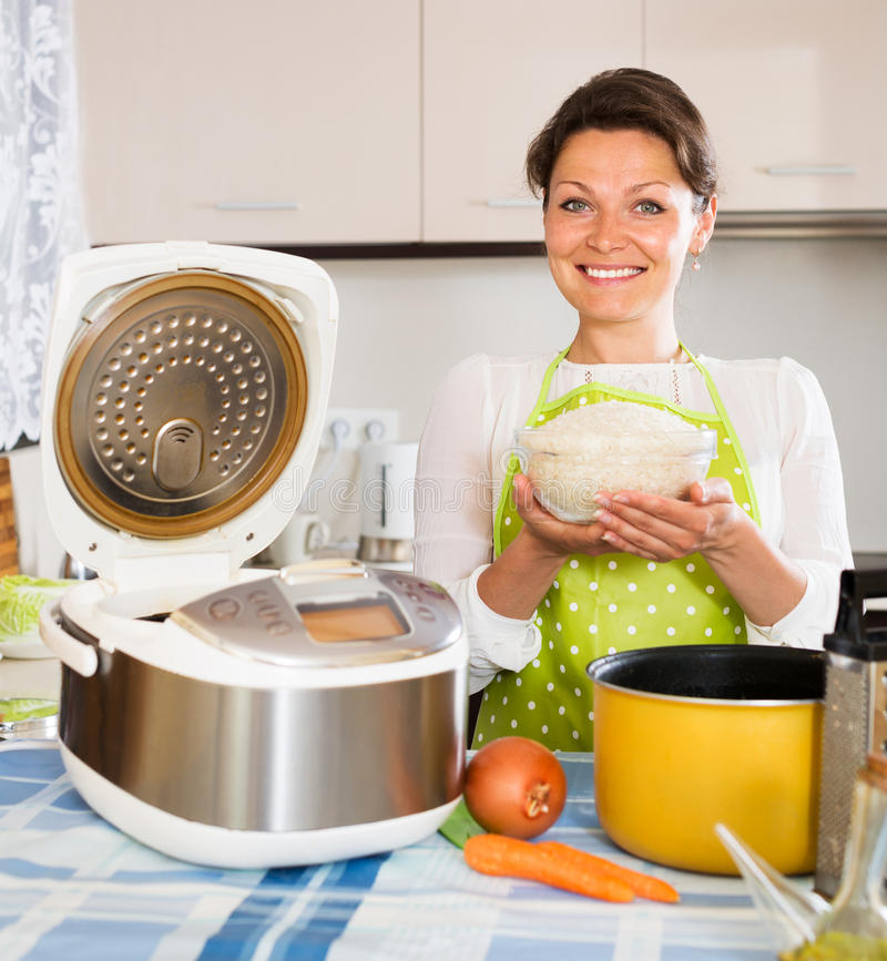 Housewife cooking rice with multicooker royalty free stock images