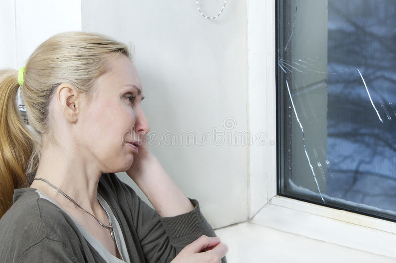 Housewife cries, bad quality window has burst because of cold weather. The housewife cries, bad quality window has burst because of cold weather stock photos