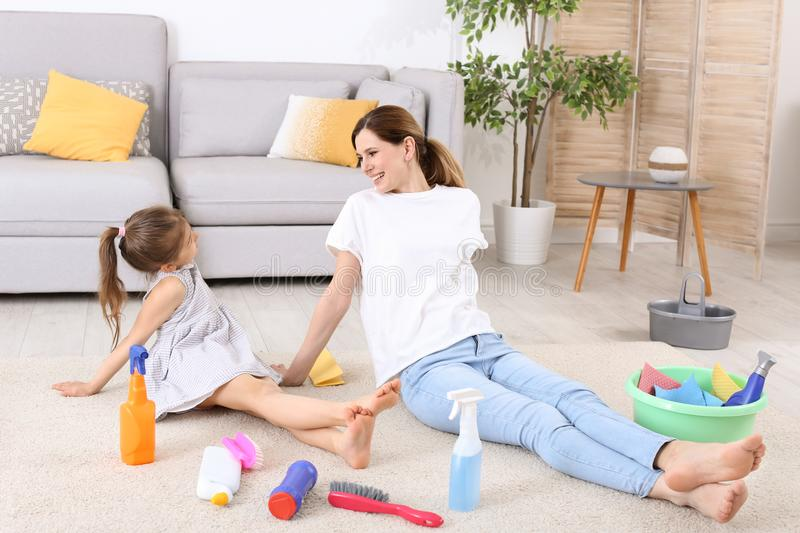 Housewife and daughter resting after cleaning stock photography