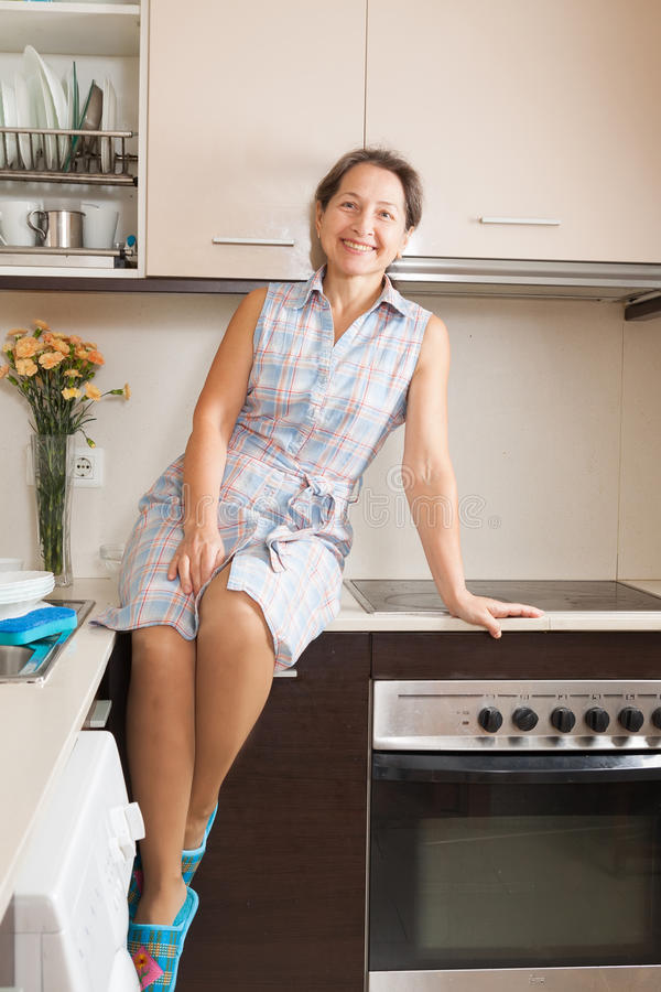 Housewife at domestic kitchen. Smiling woman on table of domestic kitchen stock photo
